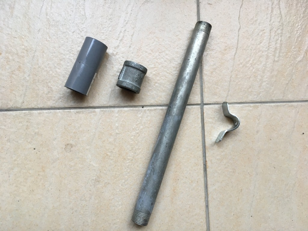 Metal pipe, pipe connector, pvc connector, and bent metal piece on tiled floor