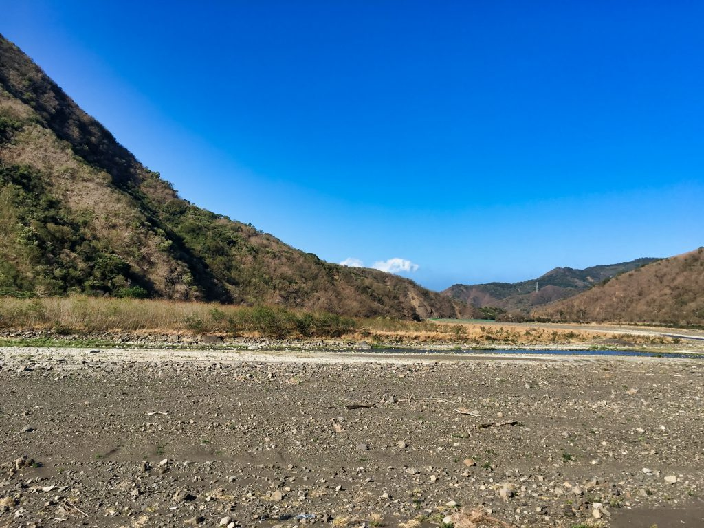 Mostly dry riverbed - watermelons planted - mountains and blue sky