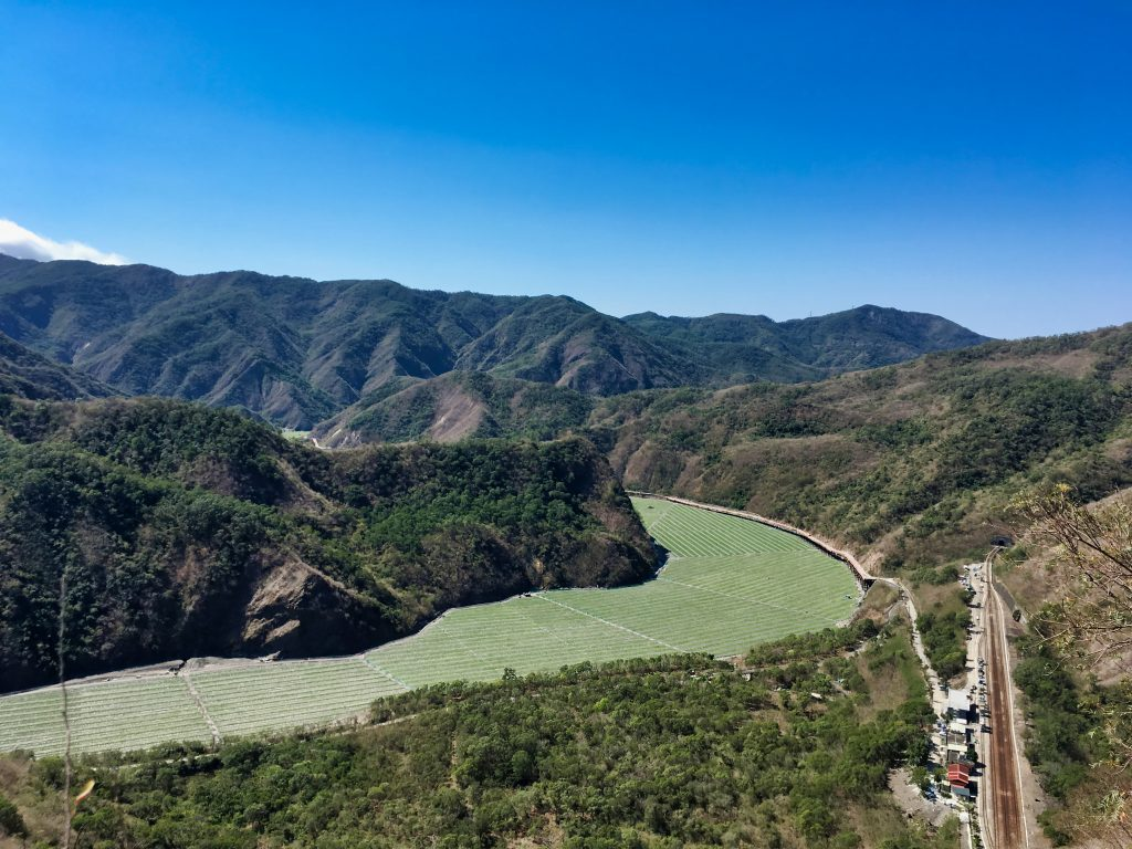 Looking down at watermelon fields planted in dry riverbed - blue sky and mountains - train relay station
