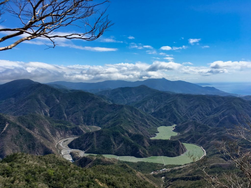 Looking down at watermelon fields planted in dry riverbed - blue sky and mountains - ocean in distance