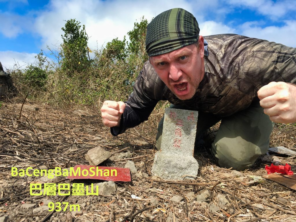 Man posing victoriously behind triangulation stone for 巴層巴墨山