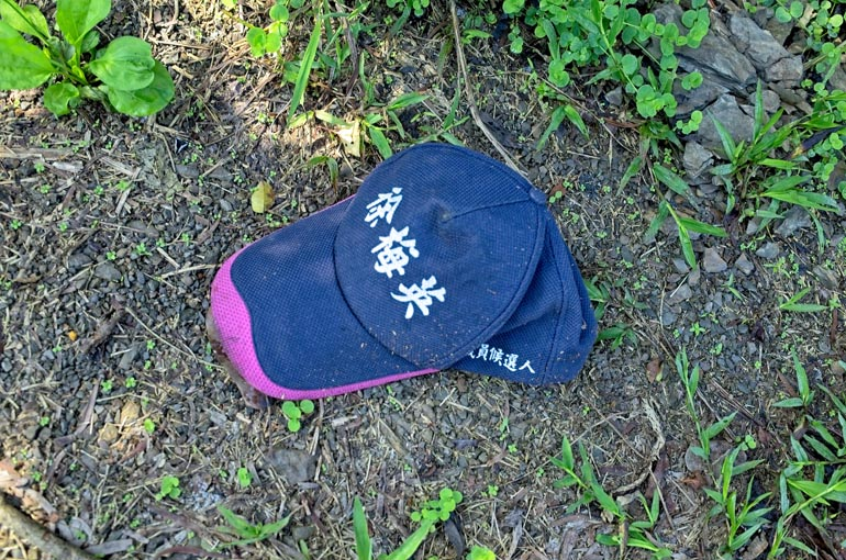 Baseball cap on ground with Chinese words written on it