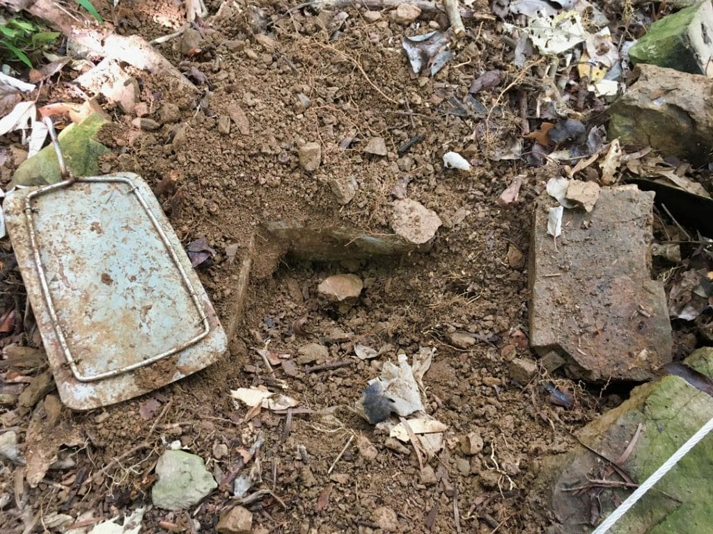 Rectangular hole dug with metal plate on top