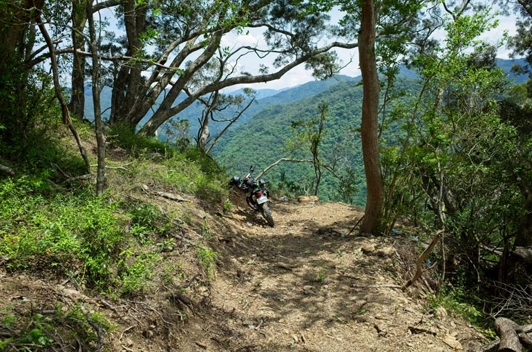 Mountain trail ending suddenly - motorcycle parked near edge