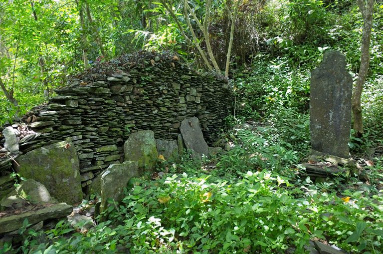 Half wall of aboriginal house - stacked rocks in middle of grass and other rocks