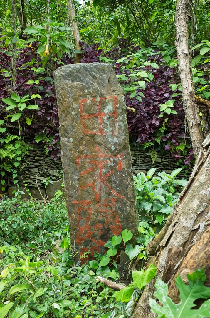 Large tall thin upright stone with words written in paint