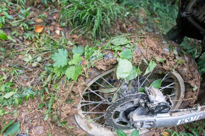 Closeup of motorcycle rear knobby tire filled with mud and leaves