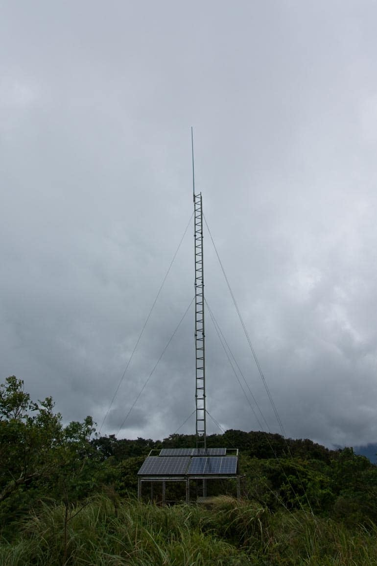 Antenna and fenced off area around it below from a distance - overcast skies above
