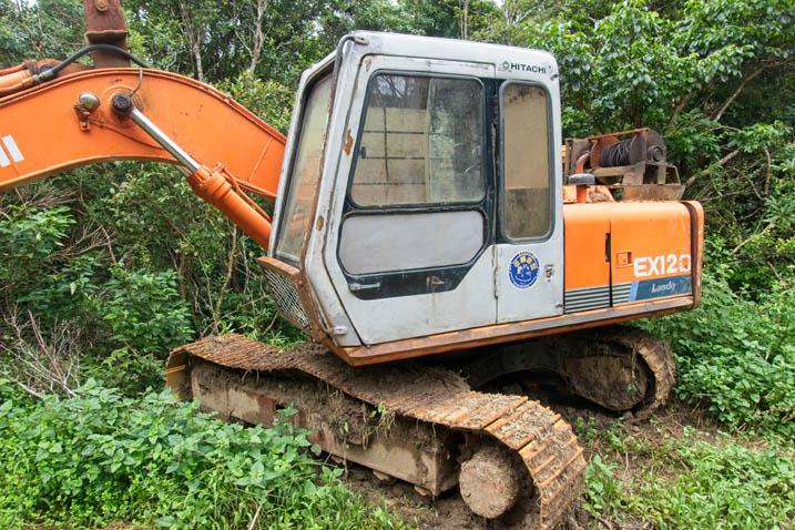 Orange excavator on side of dirt road