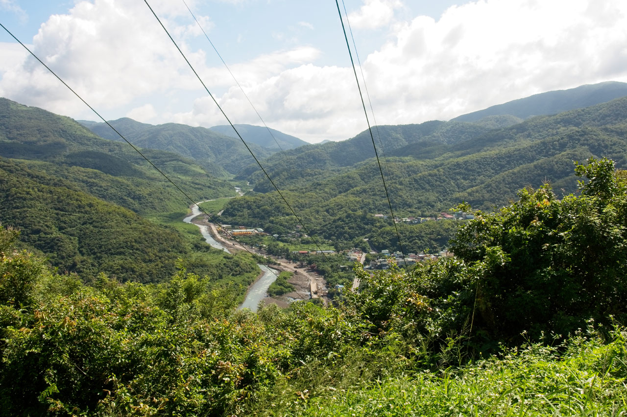 Mountains in background - small river towards left side - village on right of river - two power lines in center of picture going down to village