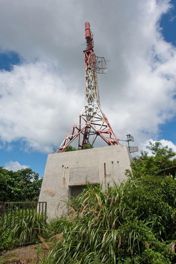 石門山 - ShiMenShan transmission station - white clouds above - large concrete structure with garage door and red and white antenna (supported by three legs) on top