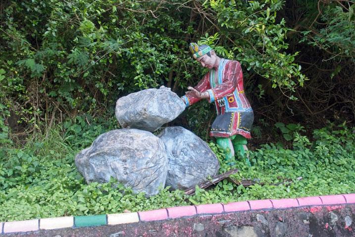 Stone aboriginal man stacking large boulders