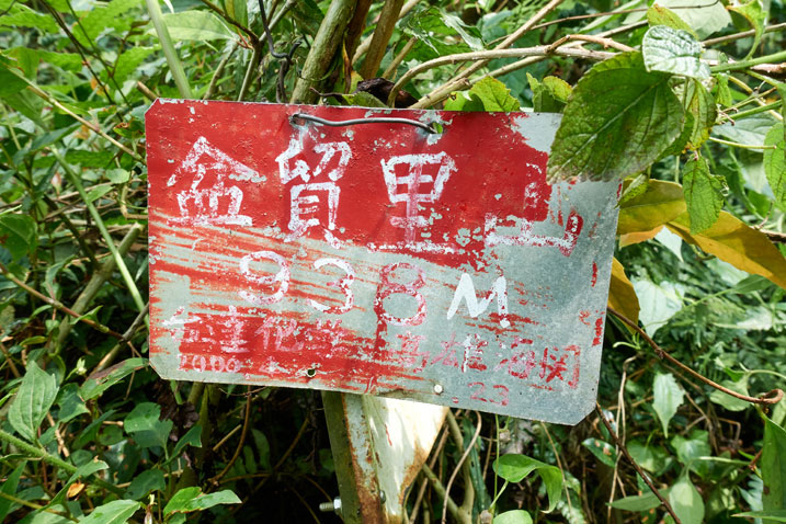 Red sign nailed to another sign - Chinese writing