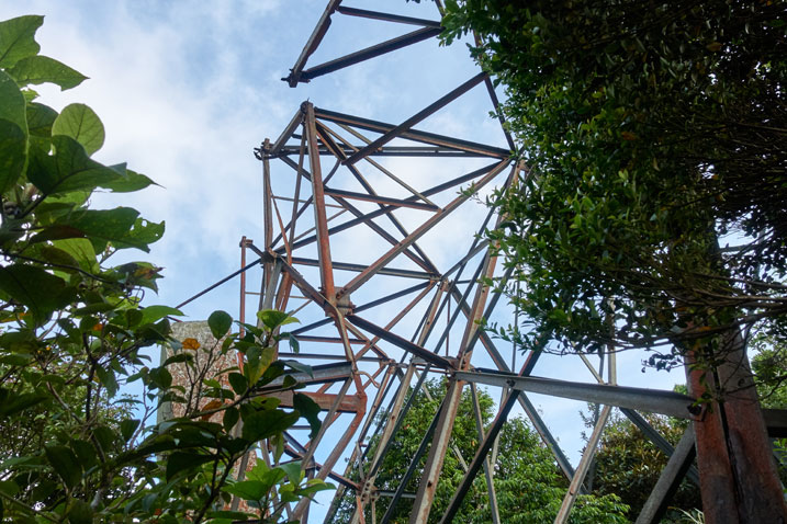 metal beam structure - broken - trees to side - blue skies above