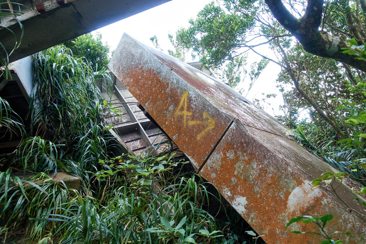 """Rusted metal box-like structure that has fallen to the ground - an """"A"""" and an arrow spray painted in yellow on it - some plants growing around it"""