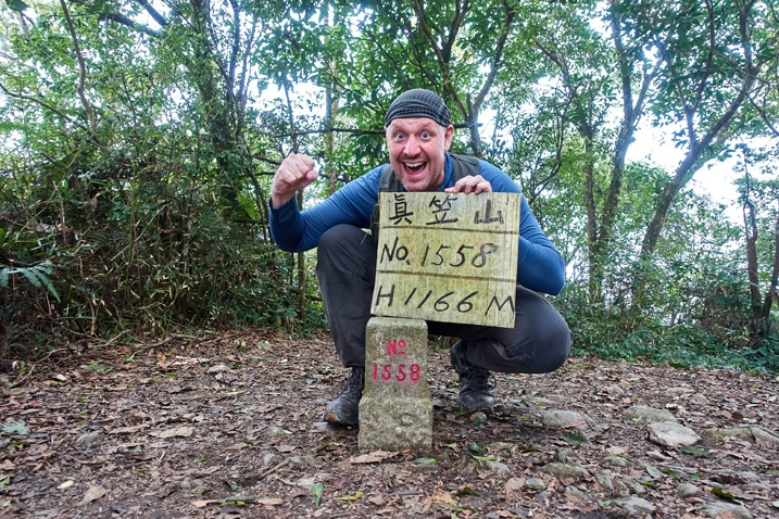 Man standing behind triangulation stone holding a sign