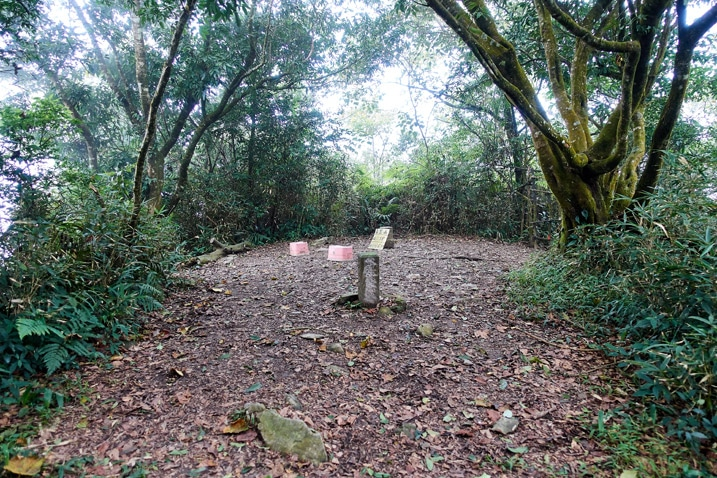 Mountain peak - open area with two stone markers and plastic stools - trees all around