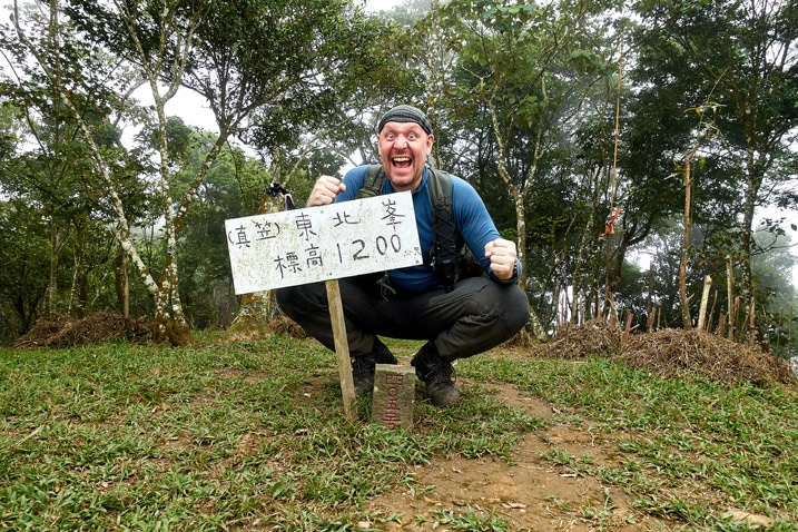 Man with triumphant pose behind a triangulation stone - holding sign