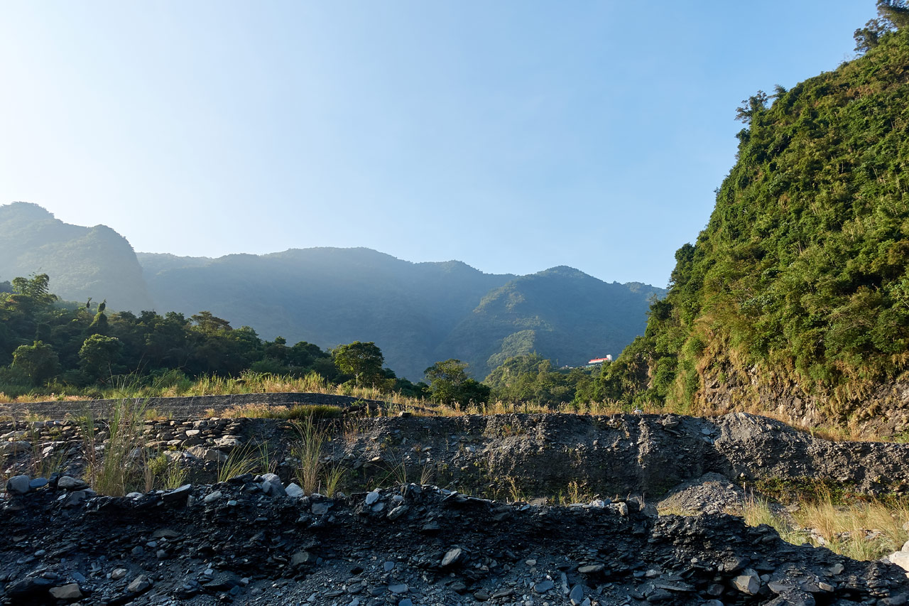 Side of rocky riverbed with mountains behind - ZuMuShan 足母山
