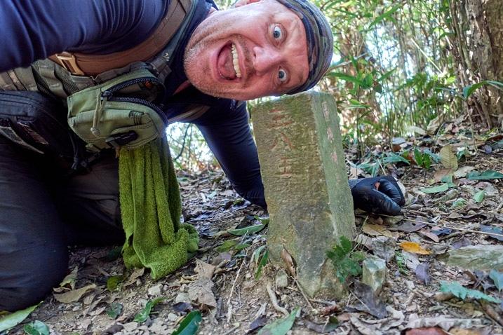 man sideways above triangulaion stone looking happy - WeiLiaoShan Hike – 尾寮山