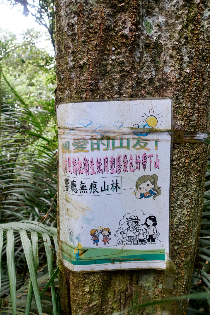 A sign in chinese attached to a tree - WeiLiaoShan 尾寮山 trail
