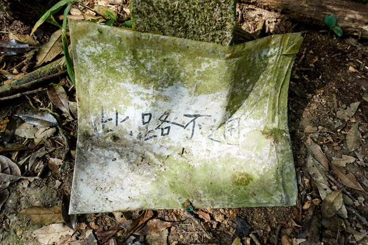 A moldy paper sign with Chinese writing - WeiLiaoShan 尾寮山 trail