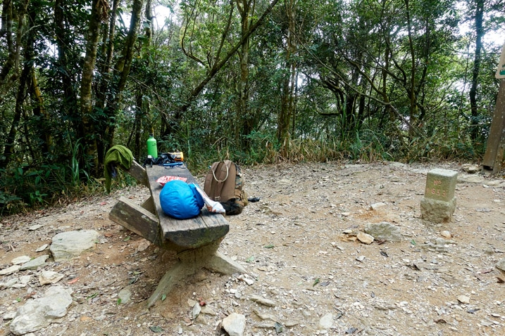 Open area with a small bench with gear on top and backpack nearby - WeiLiaoShan 尾寮山