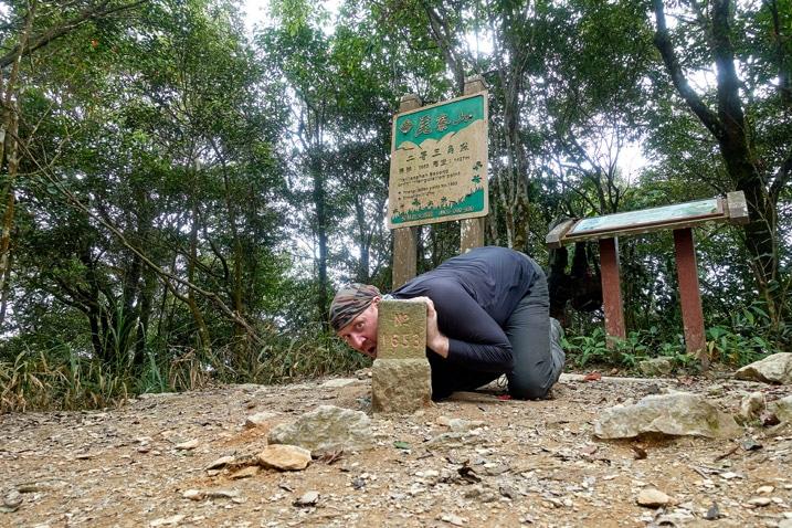 Man posing by triangulation stone - WeiLiaoShan 尾寮山