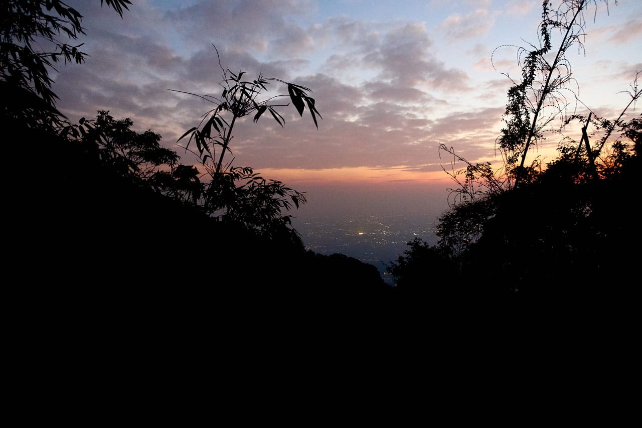 Sun setting - looking at city below - black trees in foreground - WeiLiaoShan 尾寮山 trail