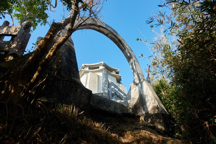 Looking up at a circular arch opening - white building behind it - 旗月縱走 - 旗尾山