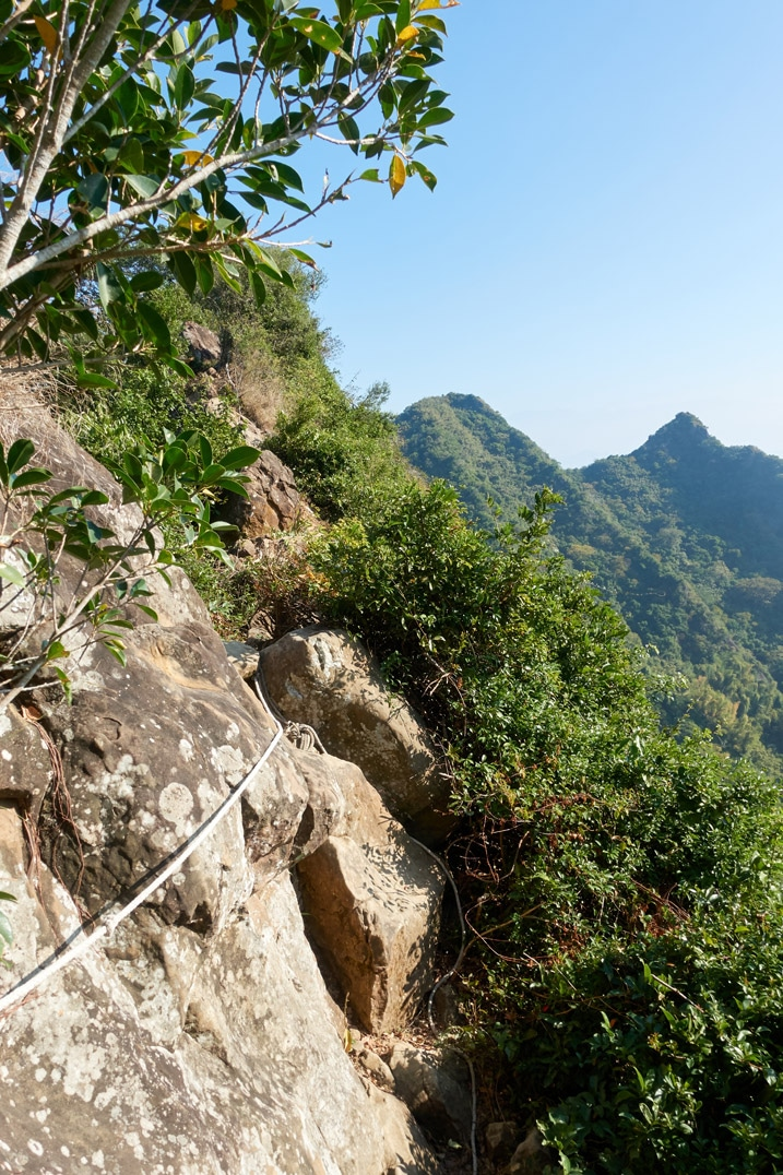 Rocky rope section of trail with mountains in backround - 旗月縱走