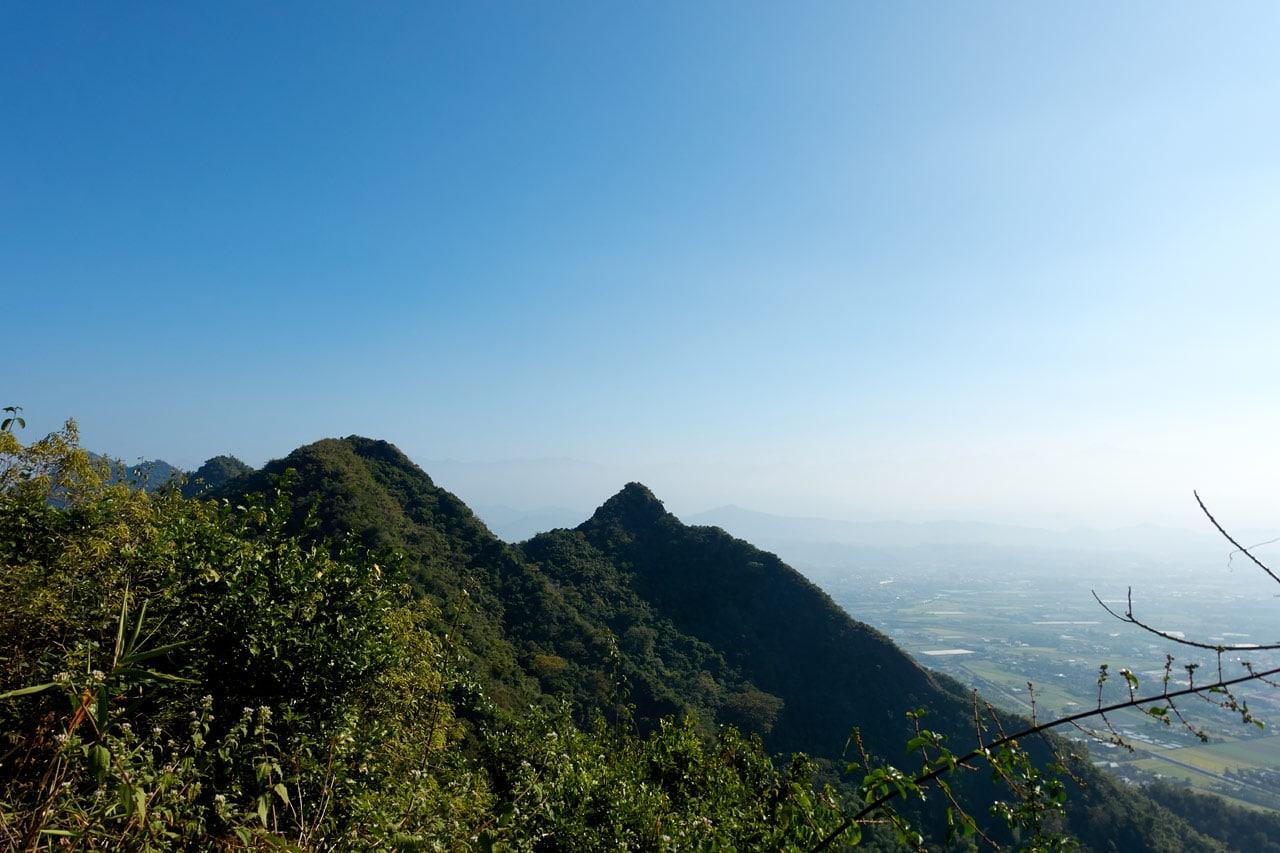 Two low mountain peaks and farmland below - blue skies - 旗月縱走