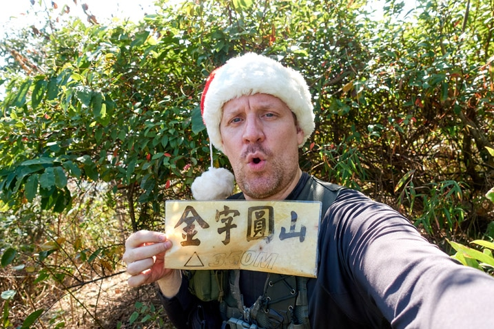 Man in Santa hat holding yellow sign in Chinese - 旗月縱走 - 金字圓山