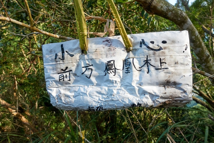 White sign with Chinese hanging from tree - 旗月縱走