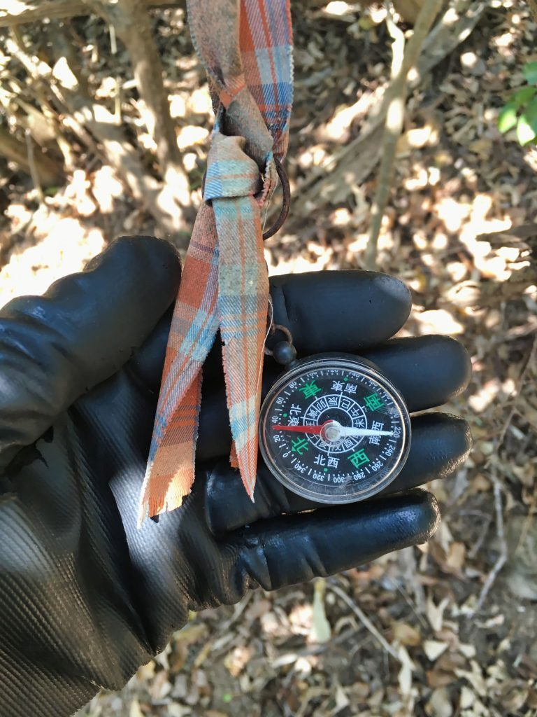 Gloved hand holding compass in Chinese attached to torn cloth
