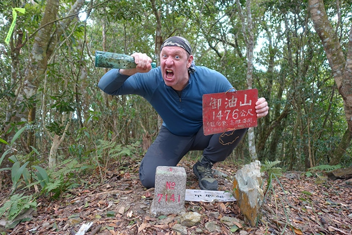 Man kneeling behind triangulation stone pretending to drink from a bottle - holding red sign - 御油山 - YuYouShan