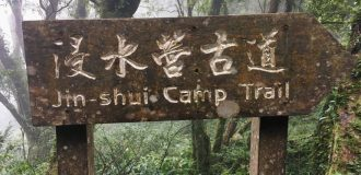 "Wooden sign in forest that says ""JinShui Camp Trail – 浸水營古道"