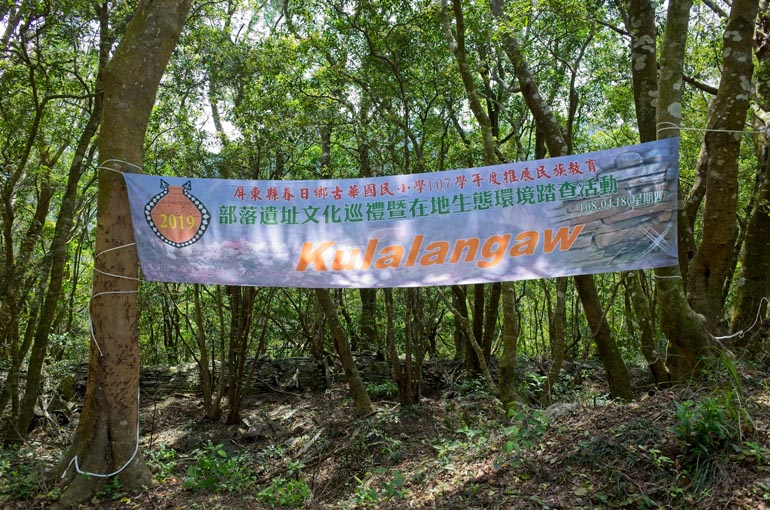 A banner strung from tree to tree with Chinese and Kulalangau written on it