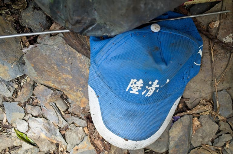 Blue cap with white Chinese writing lying on the ground
