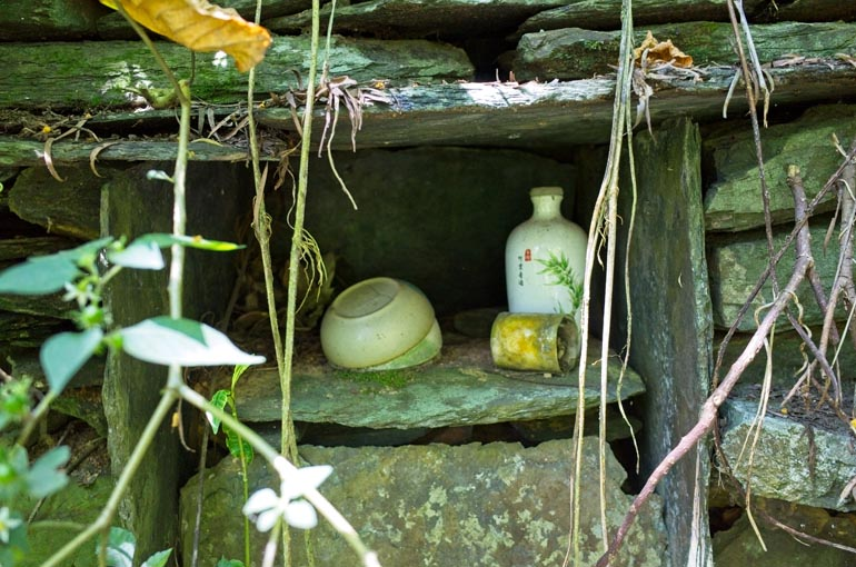 Altar within stone foundation - bowls, candle and decorated vase or bottle inside