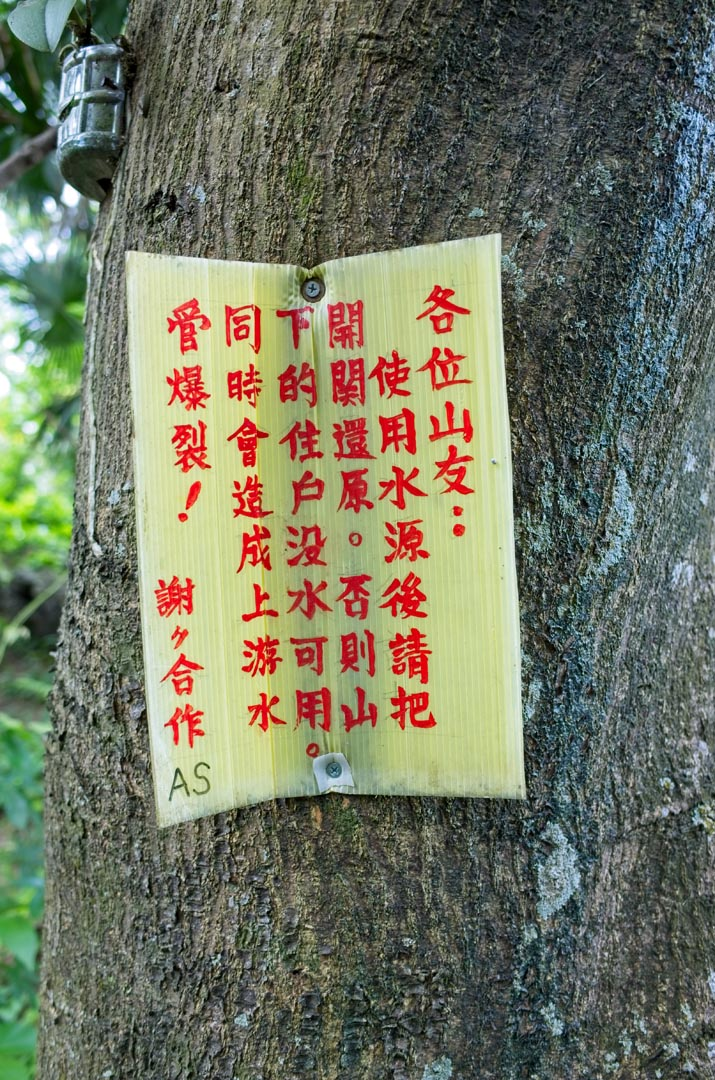 Sign in Chinese - red letters - nailed to tree