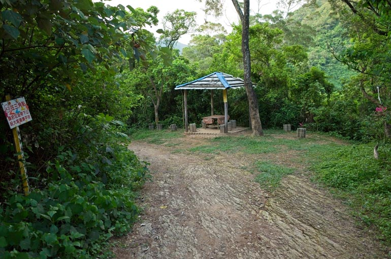 Dirt road passing a gazebo with stone chairs and a table