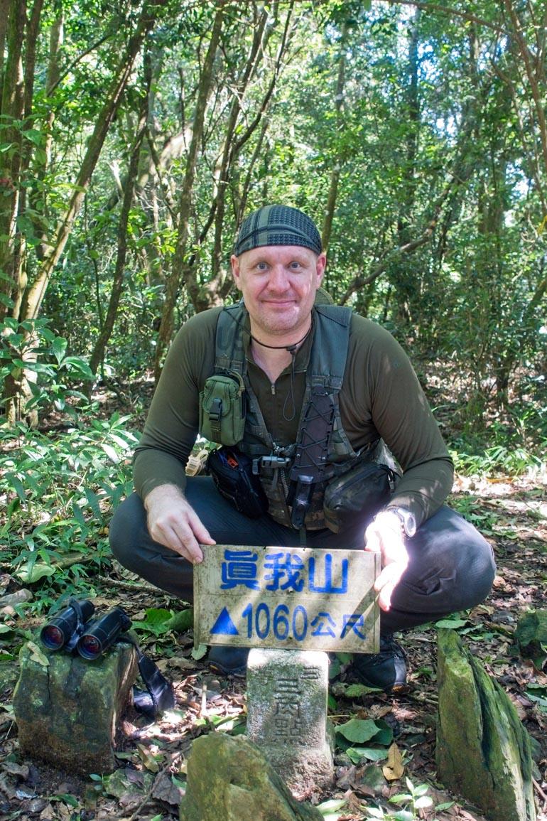 Me squatting behind the 真我山 Zhenwoshan triangulation marker holding the peak sign