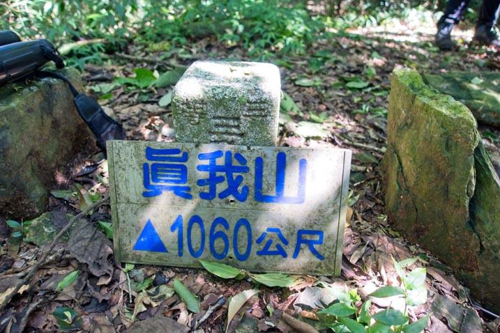 真我山 Zhenwoshan triangulation marker with peak sign leaning against it