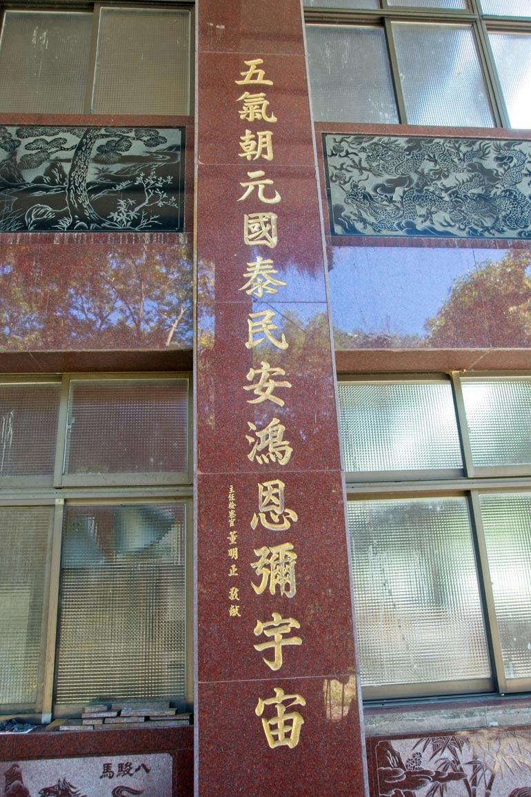Windows and carving in side of building - Chinese words written down side