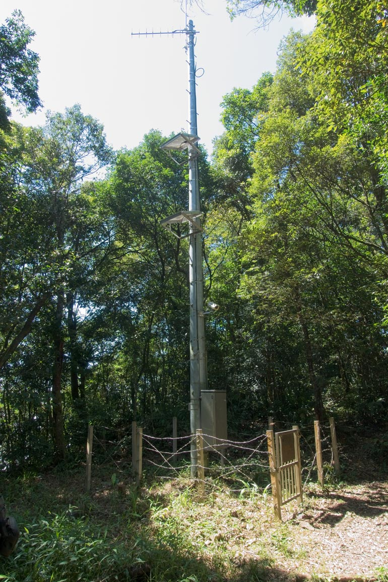 A long antenna surrounded by a barbed wire fence - trees behind it