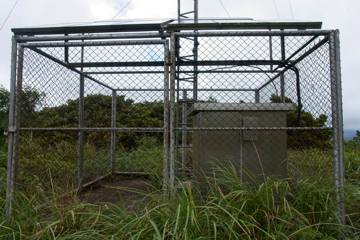 Base of antenna and large metal enclosure surrounded by a fence