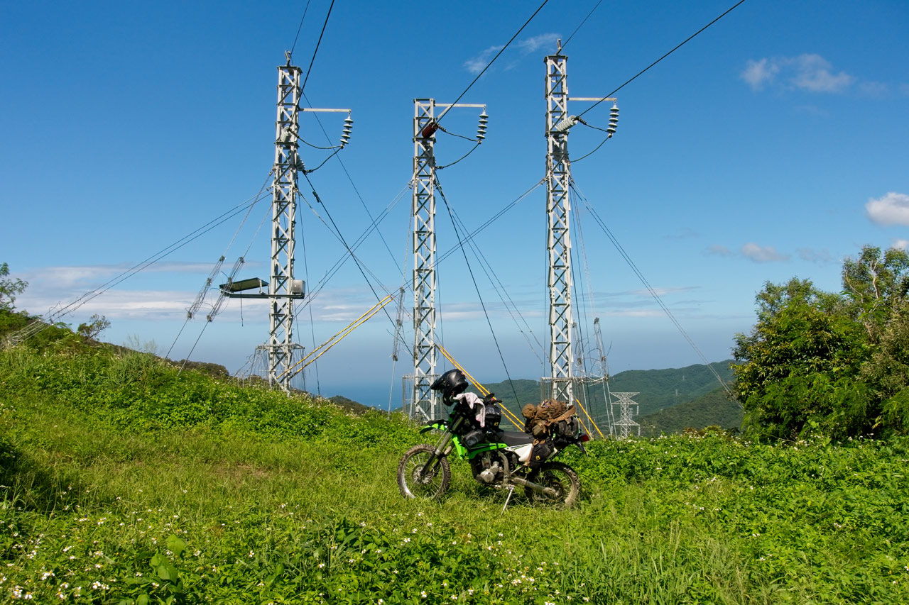 Motorcycle in open field - small power lines behind bike - blue skies and mountains and ocean barely visible in background