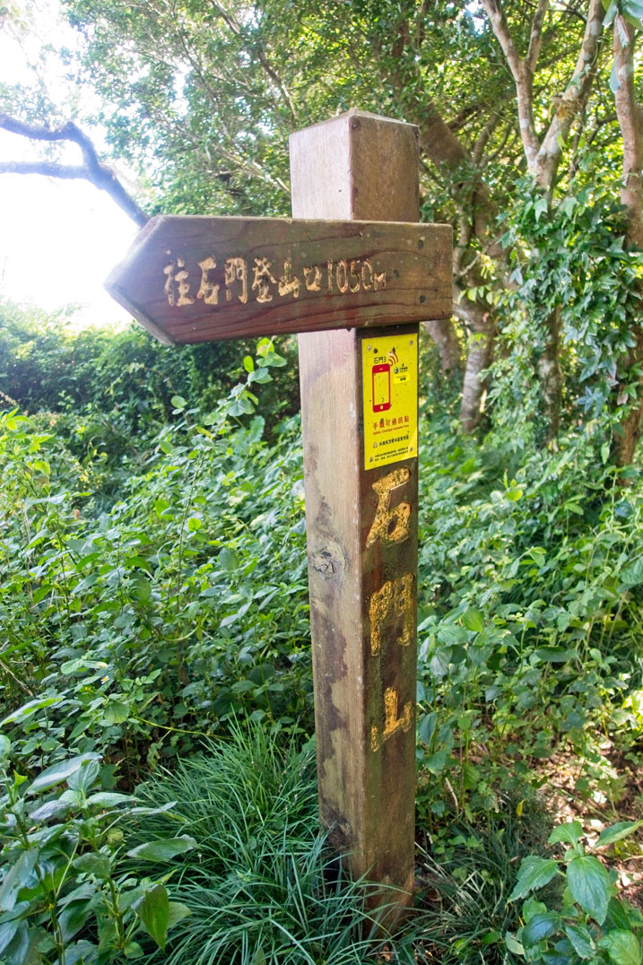 Taller wooden pillar with 石門山 written on it - yellow sign attached saying cellphone service is here