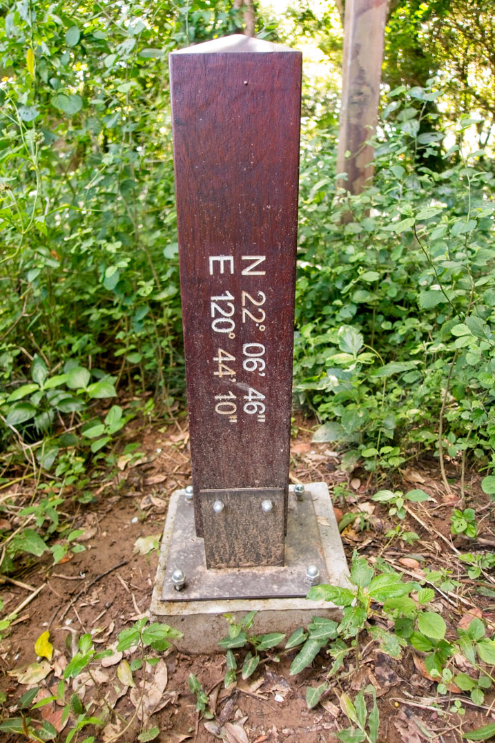 Side of wooden pillar that has the coordinates of this location written on it